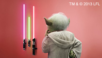 Yoda studying lightsabers of different length