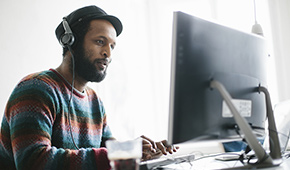 Man wearing headphones while using his computer