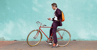 Man on bicycle looking at phone