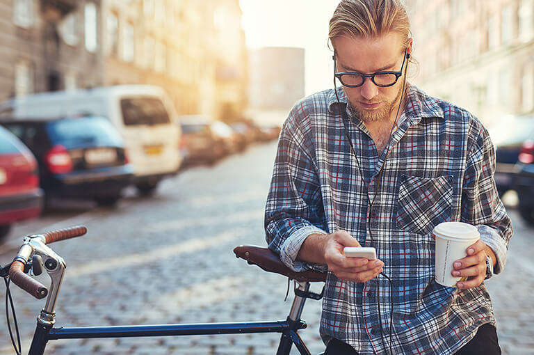 Man leaning on a bike looking at his phone