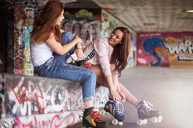 Two girls sitting down with roller skates on