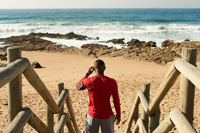 man on a beach with earphones in